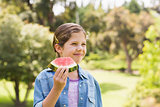 Smiling young girl eating water melon in park