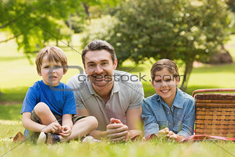 Smiling father with young kids lying on grass in park