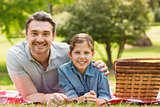 Smiling father with daughter lying on grass in park
