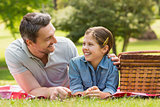Smiling father with young daughter lying on grass in park