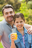 Smiling father with young daughter holding orange juice in park