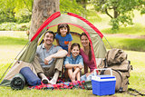 Couple with kids sitting in the tent at park