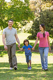 Family of three holding hands and walking at park