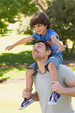 Smiling man carrying son on his shoulders in park