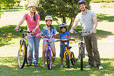Family of four with bicycles in the park