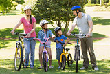 Family of four with bicycles in park