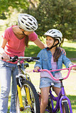 Smiling woman with her daughter riding bicycles