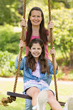 Happy mother pushing daughter on swing