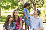 Couple with young kids sitting on park bench