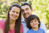 Closeup of a smiling couple with son in park