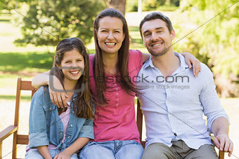 Smiling couple with daughter on park bench