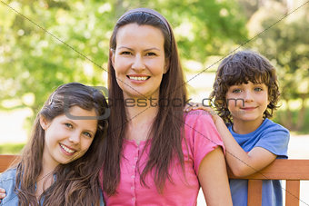 Smiling woman with kids sitting on park bench