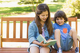 Kids reading book on park bench