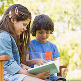 Side view of kids reading book on park bench