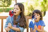 Kids blowing pinwheels on park bench