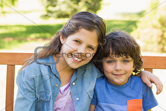 Portrait of cute kids sitting on park bench