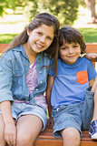 Young boy and girl sitting on park bench