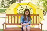 Girl sitting on park bench with an umbrella