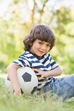 Cute little boy with football sitting on grass in park