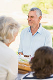 Senior man with family at outdoor dining table