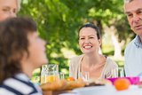 Woman sitting with family at outdoor dining table