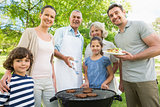 Extended family standing at barbecuing in park