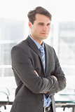 Handsome focused businessman with arms crossed