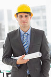 Happy architect holding blueprints looking at camera