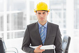 Serious architect holding blueprints looking at camera
