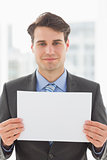 Smiling businessman holding blank page