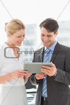 Smiling business team looking at tablet pc together