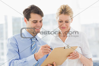 Smiling business team looking at clipboard together