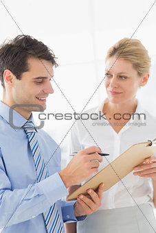 Smiling business team working from clipboard together