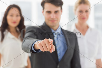 Smiling businessman pointing to camera in front of his team