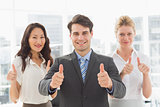 Smiling businessman giving thumbs up with his team