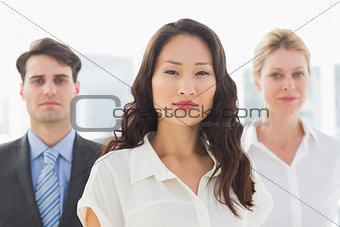 Serious businesswoman in front of her team