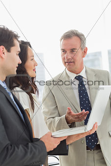 Business team standing and working on laptop together