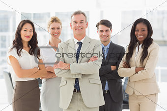 Business team smiling at camera with arms folded
