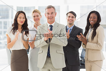 Business team standing and clapping at the camera