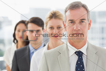 Stern business team standing in a line