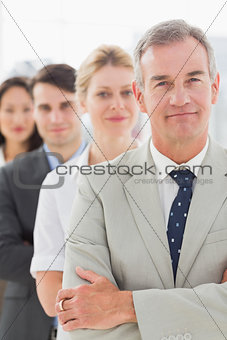 Business team standing in a line smiling at camera