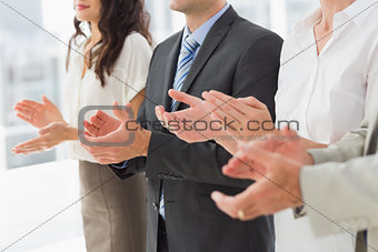 Business team standing in a row applauding
