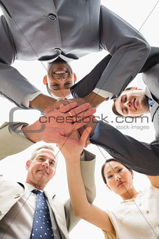 Business team smiling down at the camera with hands together