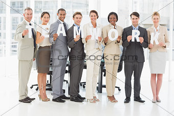 Diverse business team holding up letters spelling teamwork