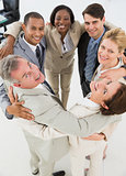 Diverse business team hugging in a circle smiling at camera
