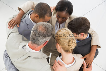 Close business team embracing in a circle