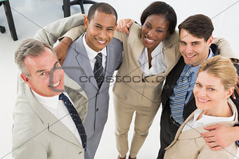 Close business team embracing and smiling up at camera