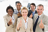 Diverse close business team smiling up at camera giving thumbs up