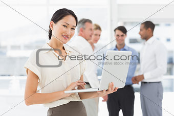 Smiling asian businesswoman using laptop with team behind her