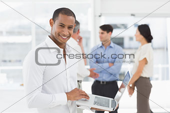 Young businessman using laptop with team behind him smiling at camera